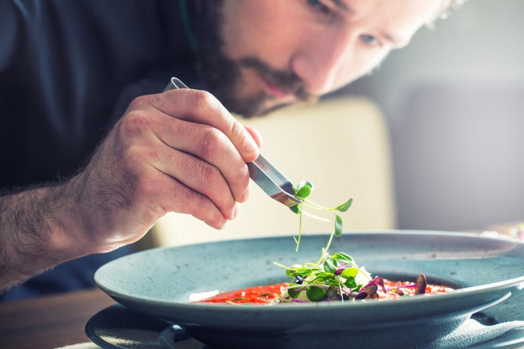 cuisinier décorant une assiette gastronomique