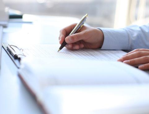 Avocat rédigeant une transmission d'entreprise